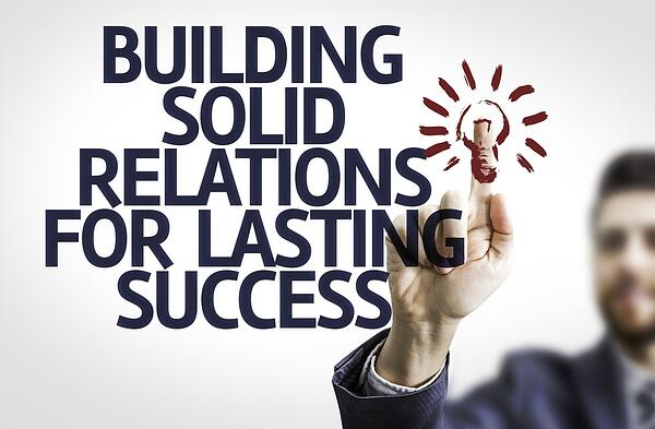 Business man pointing to transparent board with text Building Solid Relations For Lasting Success