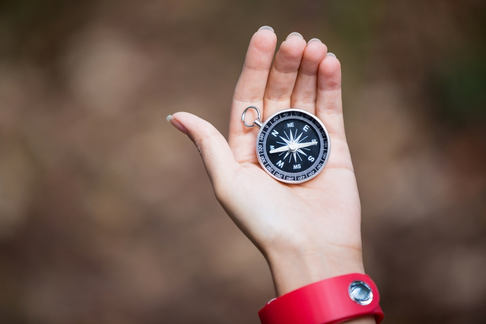 Compass in womans hand in the forest.jpeg