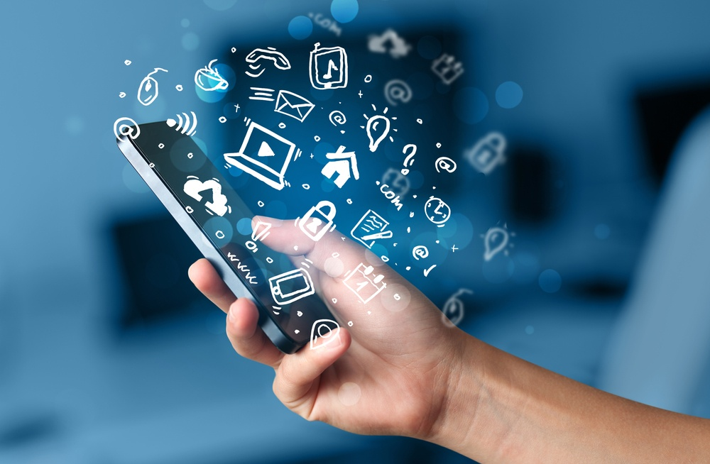 Hand holding smartphone with media icons and symbol collection